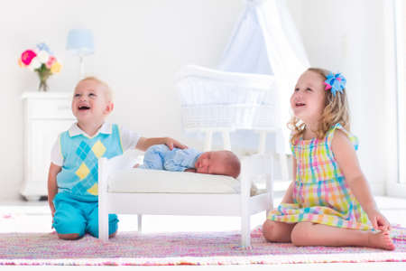babies playing: Cute little boy and girl kissing newborn brother. Toddler kids meet new born sibling at home. Infant sleeping in toy bed in white nursery. Kids playing and bonding. Children with small age difference. Stock Photo