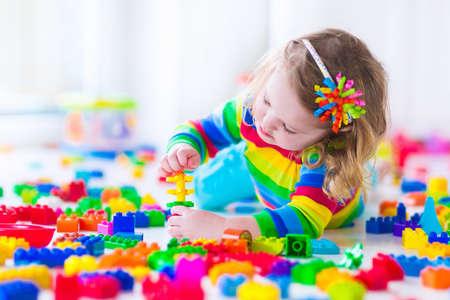 화려한 장난감 블록과 재생 미 취학 아동. 아이들은 유치원이나 보육에서 교육 장난감을 재생합니다. 유치원 아이들이 플라스틱 블록 타워를 구축 할