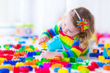 école maternelle: Enfant d'âge préscolaire enfant jouant avec des blocs de jouets colorés. Les enfants jouent avec des jouets éducatifs à la maternelle ou à la garderie. Enfants d'âge préscolaire construisent tour avec bloc en plastique. enfant en bas âge dans les écoles maternelles.