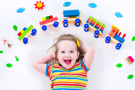 kindergarten education: Child playing with wooden train. Toy railroad for kids. Toddler kid at day care. Educational toys for preschool and kindergarten child. Little girl at daycare.