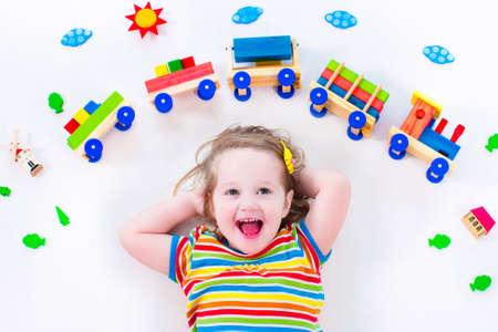 Kind spielt mit Holzeisenbahn. Spielzeug-Eisenbahn für Kinder. Kleinkind Kind am Tagespflege. Pädagogische Spielwaren für Kinder im Vorschul und Kindergartenkind. Kleines Mädchen an Kindertagesstätten. Standard-Bild