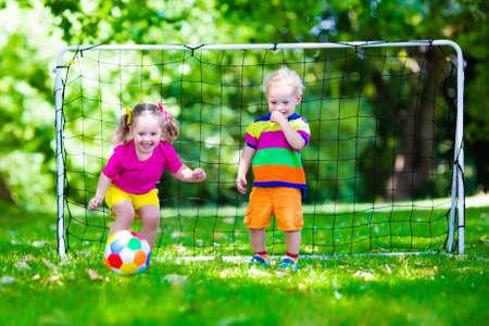 jovenes felices: Dos niños felices jugando fútbol europeo al aire libre en el patio de la escuela. Los niños juegan al fútbol. Deporte activo para el niño preescolar. Juego de bola para el joven equipo chico. Niño y niña marcar un gol en el partido de fútbol. Foto de archivo