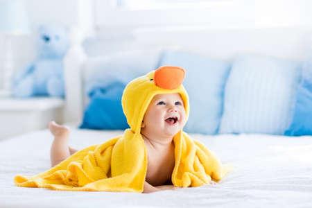 목욕이나 샤워 후 침대 부모에 앉아 노란색 후드 오리 수건을 입고 행복한 웃고 아기. 침실에 깨끗하고 건조 아이. 입욕과 작은 아이의 세척. 어린이 위