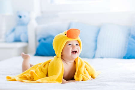 bañarse: bebé que ríe feliz en color amarillo toalla con capucha de pato que se sienta en cama de los padres después del baño o ducha. niño limpio y seco en el dormitorio. Bañarse y lavar de los niños pequeños. Niños higiene. Textil para los niños.