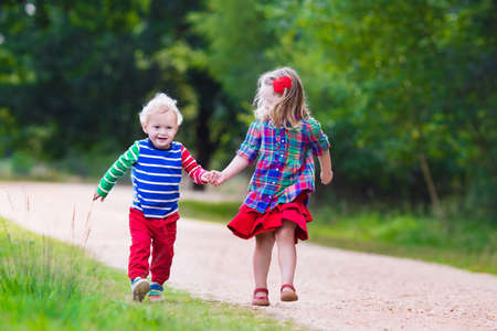 two children: Kids playing in autumn park. Children play outdoors on a sunny fall day. Boy and girl running together hand in hand in a forest. Toddler and preschooler pick colorful oak leaf. Family fun outdoor.