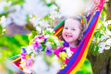 niños riendose: Niño que se relaja en hamaca. Niña linda del niño que juega en un jardín de los cerezos en flor soleado con flores blancas. Niños que se divierten comiendo manzana para la merienda saludable durante las vacaciones de primavera en una granja con huerto de árboles frutales.