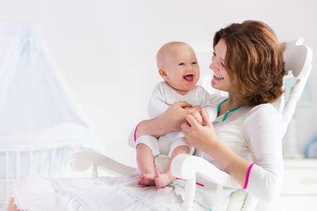 Une jeune mère tenant son enfant nouveau-né. Soins infirmiers maman bébé. Femme et le nouveau garçon né dans la chambre blanche avec chaise berçante et berceau bleu. Intérieur pépinière. Mère jouant avec rire gamin. Famille à la maison
