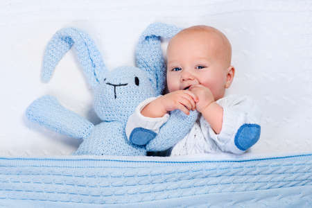 knitting: Funny little baby wearing a warm knitted jacket playing with toy bunny relaxing on white cable knit blanket in sunny nursery. Kids winter clothing and bedding. Hand made toys and textile for children. Stock Photo