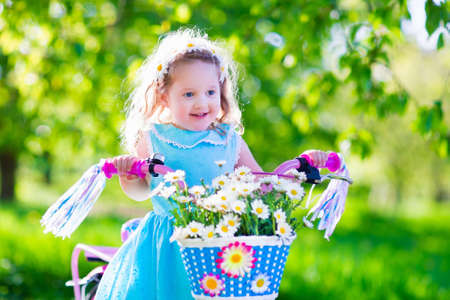 kids outside: Happy child riding a bike. Cute kid biking outdoors. Little girl in a blue dress on a pink bicycle with daisy flowers in a basket. Healthy preschool children summer activity. Kids playing outside. Stock Photo
