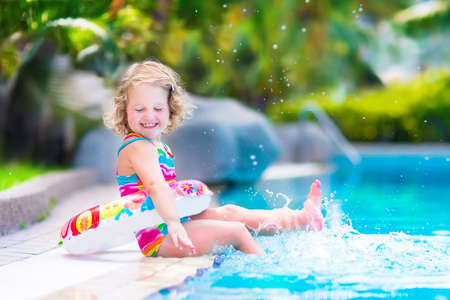caucasian: Adorable little girl with curly hair wearing a colorful swimming suit playing with water splashes at beautiful pool in a tropical resort having fun during family summer vacation Stock Photo