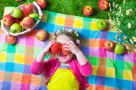 peek: Child eating apple. Little girl playing peek a boo holding fresh ripe apples. Kids eating snack relaxing on a lawn. Children summer fun on a farm picking healthy fruit. Stock Photo