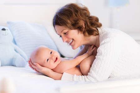 Moeder en kind op een witte bed. Moeder en baby jongen in luier spelen in het zonnige slaapkamer. Ouder en klein kind ontspannen thuis. Gezin plezier samen. Beddengoed en textiel voor baby kwekerij. Stockfoto