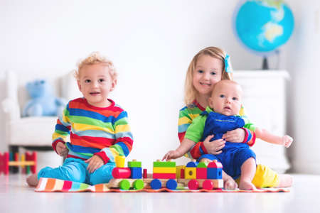 木造電車で遊んでいる子供たち。幼児子供と赤ちゃんのブロック、列車や車で遊びます。保育園と幼稚園の子供の教育おもちゃ。男の子と女の子は