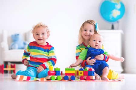 Niños jugando con el tren de madera. Niño niño y el bebé juegan con bloques, trenes y coches. Juguetes educativos para preescolar y jardín de infantes menores. El muchacho y la estructura de la muchacha ferrocarril del juguete en casa o en la guardería. Foto de archivo - 54638960