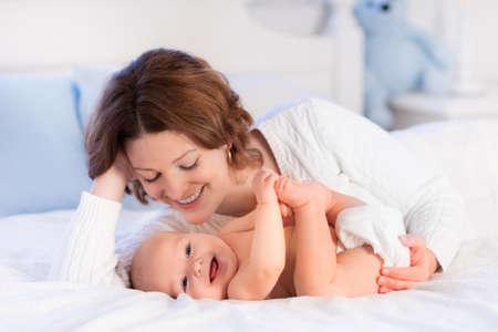 garderie: Mère et enfant sur un lit blanc. Maman et bébé en couche-culotte jouant dans la chambre ensoleillée. Parent et petit enfant détente à la maison. Famille avoir du plaisir ensemble. Literie et textile pour une pouponnière.