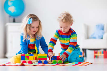 Kinderen spelen met houten trein. Peuter jongen en baby spelen met blokken, treinen en auto's. Educatief speelgoed voor voorschoolse en kleuterschool kind. Jongen en meisje build speelgoed spoorlijn thuis of kinderdagverblijf. Stockfoto