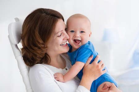 Junge Mutter mit ihrem neugeborenen Kind. Mom Baby-Pflege. Frau und neugeborene Junge im weißen Schlafzimmer mit Schaukelstuhl und blau Krippe. Nursery inter. Mutter spielt mit Kind lachen. Familie zu Hause Standard-Bild