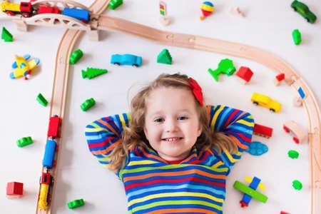 Kinderen spelen met houten trein, rails en auto's. Toy spoorweg voor kinderen. Educatief speelgoed voor kleuters en kleuters. Meisje bij de kinderopvang. Mening van hierboven, kid spelen op de vloer.