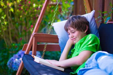 Happy school boy mit einem Buch in den Hinterhof. Kind entspannt in einer Gartenschaukel mit Bücher. Kinder während der Sommerferien zu lesen. Kinder beim Lernen. Teenager Kind die Hausaufgaben im Freien.