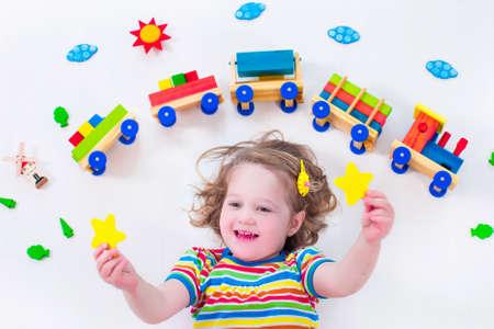나무 기차 노는 아이. 아이들을위한 장난감 철도. 보육 유아 아이. 유치원 및 유치원 아동을위한 교육 장난감. 놀이방에서 어린 소녀입니다.