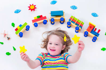 baby blocks: Child playing with wooden train. Toy railroad for kids. Toddler kid at day care. Educational toys for preschool and kindergarten child. Little girl at daycare.