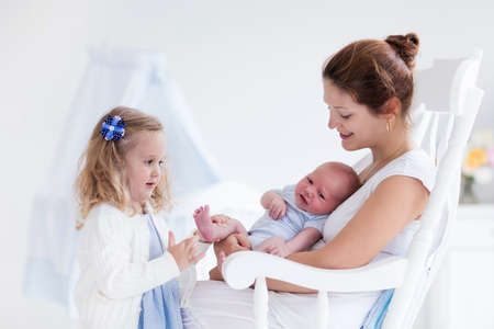 nursing sister: Little sister hugging her newborn brother. Toddler kid meeting new sibling. Mother and new born baby boy relax in a white bedroom. Family with children at home. Love, trust and tenderness concept.