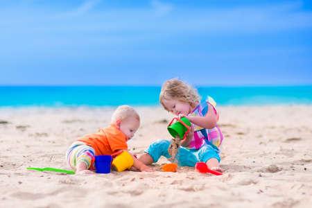 niño y niña: Los niños juegan en una playa. Niños que construyen castillos de arena en la isla tropical. Diversión en el agua de verano para la familia. Niño y niña con cubos de juguete y pala en la orilla del mar. Vacaciones Océano con el bebé y niño pequeño.