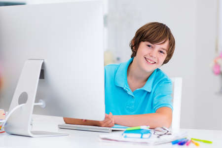 School boy working on personal computer at home. Student doing homework using modern pc in classroom. Kids studying with digital devices. Children study in white class room. Child learning.