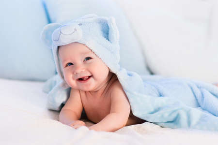 towel: Baby boy wearing diaper and blue towel in white sunny bedroom. Newborn child relaxing in bed after bath or shower. Nursery for children. Textile and bedding for kids. New born kid with toy bear.
