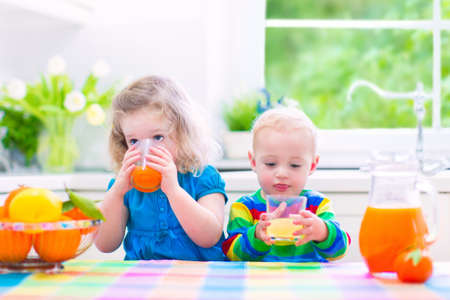ni�os desayuno: Linda ni�a divertida y de consumo del muchacho adorable beb� reci�n exprimido zumo de naranja para el desayuno saludable en una cocina blanca con ventana en una soleada ma�ana de verano Foto de archivo