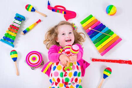 pandero: Niño con los instrumentos musicales. La educación musical para niños. Juguetes coloridos del arte de madera para niños. Niña que juega música. Cabrito con el xilófono, guitarra, flauta. Foto de archivo