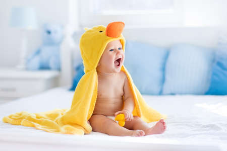 Het gelukkige lachende meisje dragen gele kap eend handdoek zittend op bed van de ouders na bad of douche. Schone droge kind in de slaapkamer. Baden en wassen van kleine kinderen. Kinderen hygiëne. Textiel voor baby's. Stockfoto