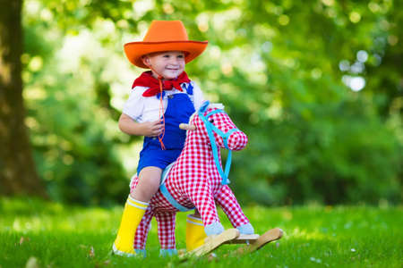 Little boy dressed up as cowboy playing with his toy rocking horse in a summer park. Kids play outdoors. Children in Halloween costumes at trick or treat. Toys for preschooler or toddler child. Banque d'images