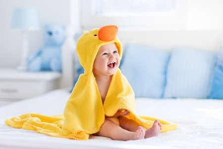 babies: Het gelukkige lachende meisje dragen gele kap eend handdoek zittend op bed van de ouders na bad of douche. Schone droge kind in de slaapkamer. Baden en wassen van kleine kinderen. Kinderen hygiëne. Textiel voor baby's. Stockfoto