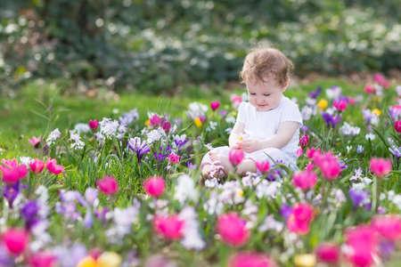 campo de flores: niña divertida hermosa jugando en un campo de flores