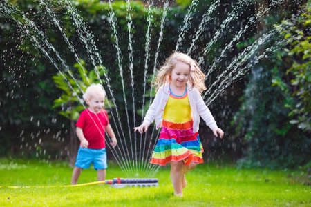 lawn sprinkler: Child playing with garden sprinkler. Preschooler kid running and jumping. Summer outdoor water fun in the backyard. Children play with hose watering flowers. Kids run and splash on hot sunny day.