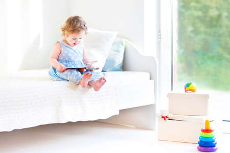 early childhood: Adorable toddler girl reading a book sitting on a white bed at a big window with garden view