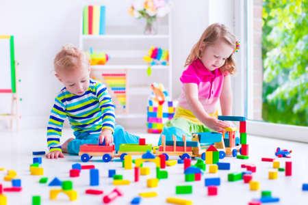 preescolar: Los niños juegan en la guardería. Dos niños niño construir torre de bloques de madera coloridos. Niño que juega con tren de juguete. Juguetes educativos para preescolar y jardín de infantes. Foto de archivo