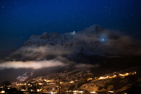 eiger: View of Eiger north face, Alps, Switzerland on clear starry night. Eiger Nordwand mountain in Swiss Bernese Alps. Mountains and snowy village in winter time with Christmas lights. Blue sky with stars.