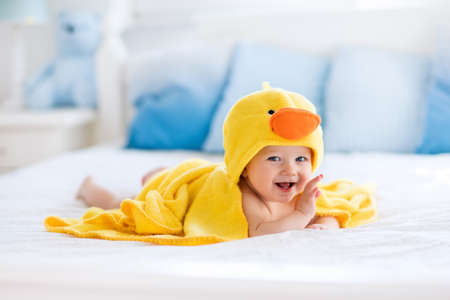 bedroom: Happy laughing baby wearing yellow hooded duck towel sitting on parents bed after bath or shower. Clean dry child in bedroom. Bathing and washing of little kids. Children hygiene. Textile for infants.