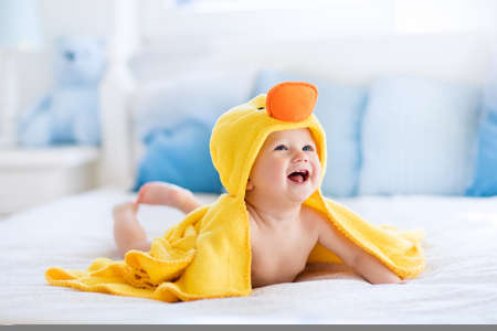 niemowlaki: Happy laughing baby noszenie żółtej kapturem ręcznik kaczka siedzi na łóżku po kąpieli rodziców. Czyste suche dziecko w sypialni. Kąpiel i mycie małych dzieci. Dzieci higieny. Tekstylia dla niemowląt. Zdjęcie Seryjne
