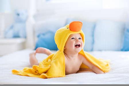Heureux bébé rire jaune portant capuche serviette de canard assis sur le lit des parents après le bain ou la douche. enfant sec propre dans la chambre. Baignade et le lavage des petits enfants. Enfants hygiène. Textile pour les nourrissons.
