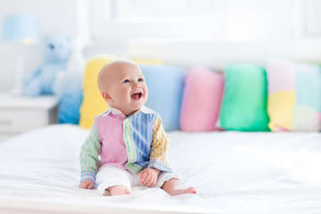 tummy time: Baby boy in white bedroom. Newborn child in bed with pastel color cushions. Nursery for children. Textile, pillows and bedding for kids. Family morning at home. New born kid tummy time with toy bear.