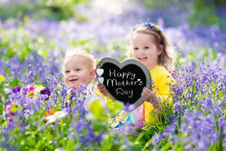 Children playing in bluebell flowers. Little girl and baby boy hold wooden heart shape chalk board. Copy space for your text. Kids having fun outdoors. Birthday or mothers day celebration.