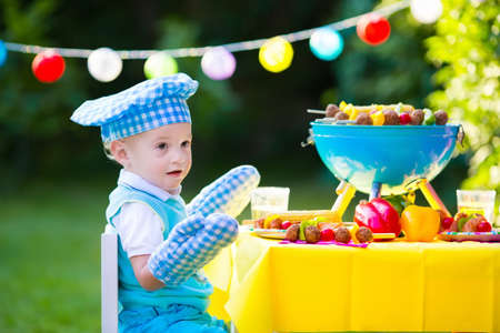 corn meal: Children grilling meat. Family camping and enjoying BBQ. Little boy at barbecue preparing steaks, kebab and corn. Kids eating grill and healthy vegetable meal outdoors. Garden party for toddler child Stock Photo