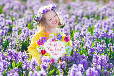 dutch girl: Child playing in hyacinth field. Little girl holding a wooden heart shape chalk board standing in a park with spring hyacinths flowers. Copy space for your text. Happy mothers day card.