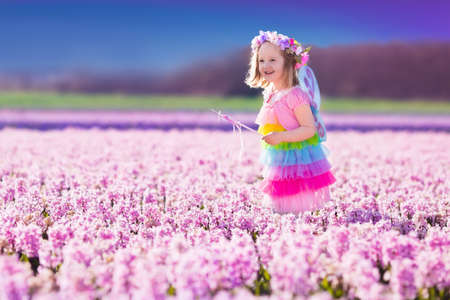 field of flowers: Beautiful girl playing in blooming hyacinth flower field. Kids princess birthday party with fairy costume, butterfly wings and magic wand. Children play in spring flowers. Child picking hyacinths.