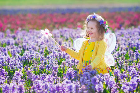 fairy garden: Beautiful girl playing in blooming hyacinth flower field. Kids princess birthday party with fairy costume, butterfly wings and magic wand. Children play in spring flowers. Child picking hyacinths.