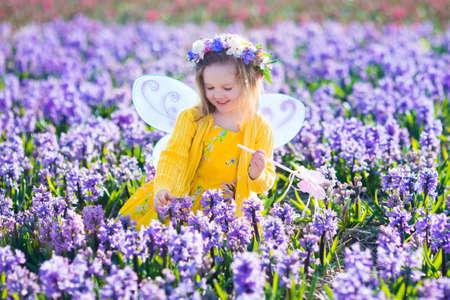 niñas bonitas: Muchacha hermosa que juega en el campo floreciente de la flor del jacinto. fiesta de cumpleaños de la princesa niños con traje de hada, alas de mariposa y la varita mágica. Los niños juegan en las flores de primavera. La cosecha del niño jacintos.
