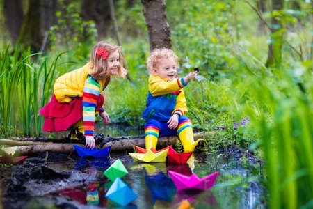 green boat: Children play with colorful paper boats in a small river on a sunny spring day. Kids playing exploring the nature. Brother and sister having fun at a forest stream. Boy and girl with toy boat and ship Stock Photo